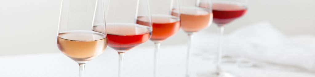 Grouping of five varieties of rose wine in wineglasses in a row.